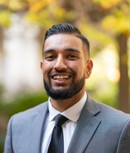Smiling young man with short beard and business attire against natural backdrop