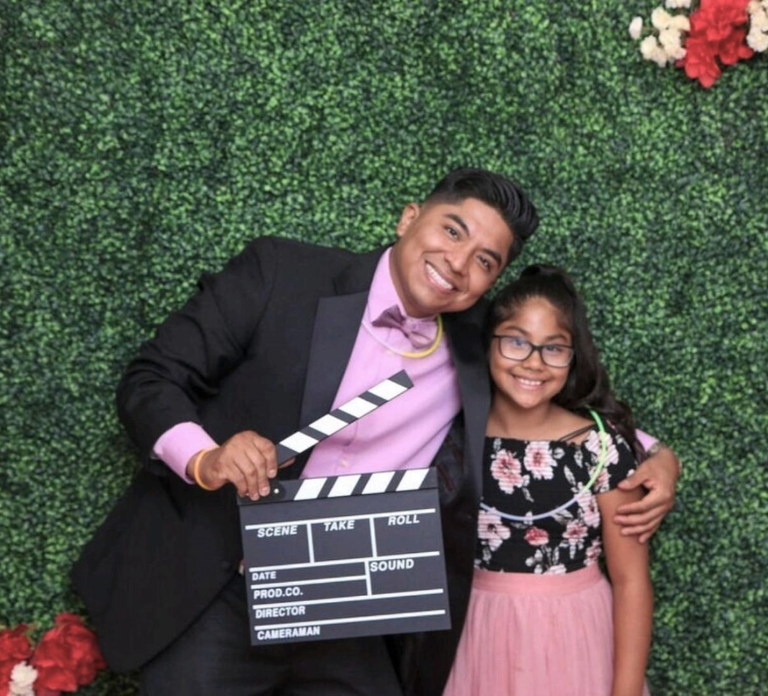YoungSmiling Latinx father and daughter in formal attire against a natural backdrop
