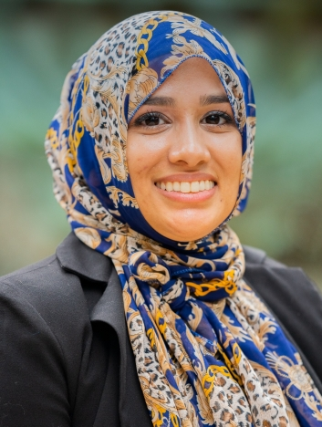 A smiling young woman in business attire and a colorful headscarf
